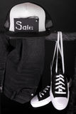 Sale sign. Black and white sneakers, cap  pant, jeans hanging on clothes rack   background.   friday. Close up. Stock Photo