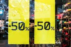 Sale sign on cloth store. Sticker  -  up to half-price 50 percent   window with clothes during winter  season Royalty Free Stock Image