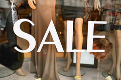 Sale sign in a fashion shop window. Selective focus on lettering Royalty Free Stock Photos