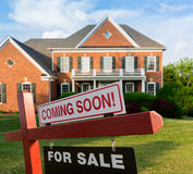 For sale sign in front of large USA home. For Sale and Coming Soon realtor sign in front of large brick single family house in expansive grass yard for real Royalty Free Stock Images
