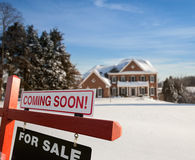 For sale sign in front of large USA home. For Sale and Coming Soon realtor sign in front of large brick single family house in expansive snow cover yard in mid Royalty Free Stock Photo