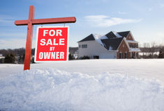 For sale sign in front of large USA home. For Sale by owner real estate sign in front of large brick single family house in expansive snow covered yard in mid Royalty Free Stock Photos