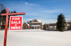 For sale sign in front of large USA home. For Sale by owner real estate sign in front of large brick single family house in expansive snow covered yard in mid Royalty Free Stock Photo