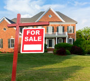 For sale sign in front of large USA home. For Sale realtor sign in front of large brick single family house in expansive grass yard for real estate opportunity Stock Images