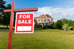 For sale sign in front of large USA home. For Sale realtor sign in front of large brick single family house in expansive grass yard for real estate opportunity Royalty Free Stock Images