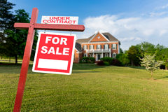 For sale sign in front of large USA home. For Sale and Under Contract realtor sign in front of large brick single family house in expansive grass yard for real Royalty Free Stock Images