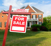 For sale sign in front of large USA home. For Sale and Under Contract realtor sign in front of large brick single family house in expansive grass yard for real Stock Image