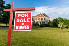 For sale sign in front of large USA home. For Sale and Under Contract realtor sign in front of large brick single family house in expansive grass yard for real Stock Photography
