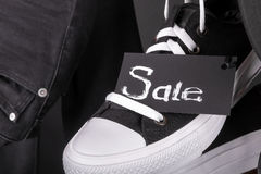 Sale sign. Hanging black and white sneakers near jeans on  background. Friday .  Close up. Stock Photos