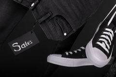 Sale sign. Hanging black and white sneakers near jeans on  background. Friday .  Close up. Stock Photography