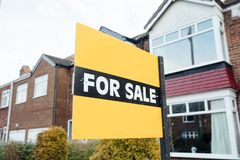 For Sale Sign on a House. `For Sale` sign outside of a terraced house in the UK Stock Image