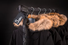 Sale sign. A lot of black coats, jacket with fur on hood hanging  clothes rack.  background.  friday.Close up. Royalty Free Stock Photos