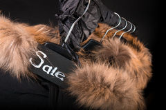 Sale sign. A lot of black coats, jacket with fur on hood hanging  clothes rack.  background.  friday. Close up. Royalty Free Stock Photography