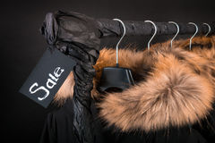 Sale sign. A lot of black coats, jacket with fur on hood hanging  clothes rack.  background.  friday. Close up. Stock Photo