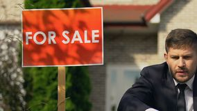 For sale sign near desperate sitting businessman, bankruptcy crisis, failure. Stock footage stock footage