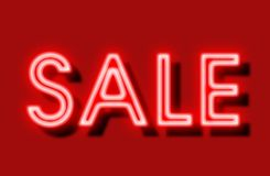Sale sign neon on red background stock images
