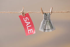 Sale sign and one hundred us dollar banknote on clothesline Stock Image