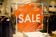 SALE Sign on the shop`s window display.discount sign on show window. Sale sign, symbol in clothes shop,The red. SALE Sign on the shop`s window display Stock Image