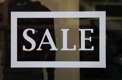 Sale sign on the shop window. Retail image of a white sale sign in a clothing store window stock image
