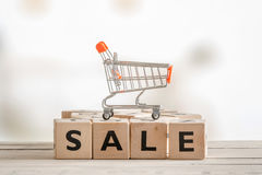 Sale sign with a shopping cart. Sale sign with a metallic shopping cart Royalty Free Stock Photography