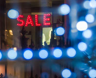 Sale Sign in Window. Red Sale SIgn Lit Up in Shop Window at Night Stock Photography