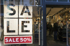 Sale signs in display window of clothing store full of customers Stock Photo