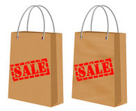 Sale signs on kraft shopping paper bags Royalty Free Stock Images
