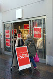 Sale signs outside clothing store on rainy street and people Royalty Free Stock Photo