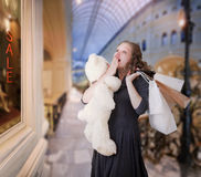 Sale in store. Portrait of young surprised woman with teddy bear and paper bags in shopping center