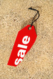 Sale Tag. Red sale label on sandy surface Stock Images