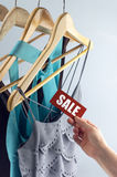 Sale tag elegant clothes. Sale, elegant clothes with tags bid, with hand stock photo