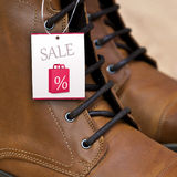 Sale Price Tag on Leather Boots. Sale tag for percentage off on brown leather boots Royalty Free Stock Image