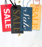 Sale Tags. Tags With Sale Sign With Stack of White Shirt in Background Stock Image