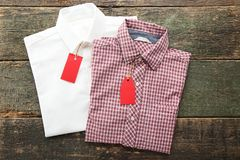 Sale tags with shirts. Sale tags with new shirts on wooden table Stock Photos