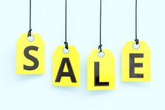 `Sale` text on yellow tags. `Sale` text on hanging yellow tags. 3d image Stock Images