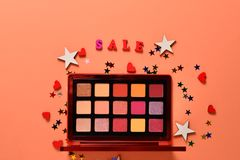 Sale text on an orange background. Professional trendy makeup products with cosmetic beauty products,  eye shadows, eye lashes,. Brushes and tools. Top view royalty free stock photos