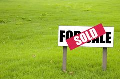 For sale then sold. Shot of a for sale sign on a plot of land covered with a sold sign Stock Photography
