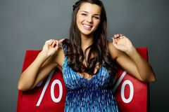 Sale time. Portrait of smiling brunette with sale paperbags looking at camera Royalty Free Stock Image
