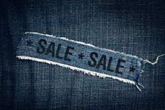SALE title on torn blue jeans texture Royalty Free Stock Photo