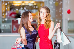 Sale, tourism, shopping and happy people concept - two beautiful women with shopping bags in the shopping center Royalty Free Stock Images