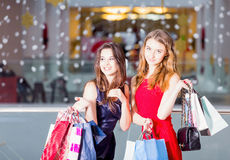 Sale, tourism, shopping and happy people concept - two beautiful women with shopping bags in the shopping center Stock Photography