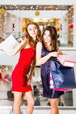 Sale, tourism, shopping and happy people concept - two beautiful women with shopping bags in the shopping center Stock Image