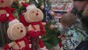 Sale of toys and Christmas trees until xmas. People in the supermarket are shopping before the new year. Christmas gifts. Christmas gifts for loved ones stock video