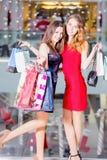 Sale, turism, shopping och lyckligt folkbegrepp - två härliga kvinnor med shoppingpåsar i köpcentret Royaltyfri Foto