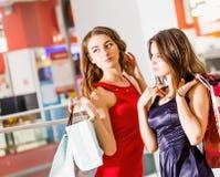Sale, turism, shopping och lyckligt folkbegrepp - två härliga kvinnor med shoppingpåsar i köpcentret Royaltyfri Bild