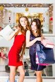 Sale, turism, shopping och lyckligt folkbegrepp - två härliga kvinnor med shoppingpåsar i köpcentret Fotografering för Bildbyråer