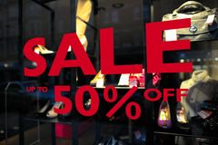 Sale (up to 50% off) sign in a fashion shop window. Selective focus on lettering Royalty Free Stock Image
