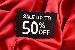 Sale upp till femtio procent etikett på den röda torkduken Arkivfoton
