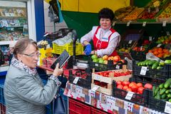Sale of vegetables and fruits from a street tray. The client and the woman-the seller of vegetables and fruits stock image