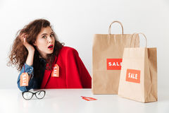 Sale woman sitting at the table with paper shopping bags. Amazed young sale woman sitting at the table with paper shopping bags isolated over white background Royalty Free Stock Image